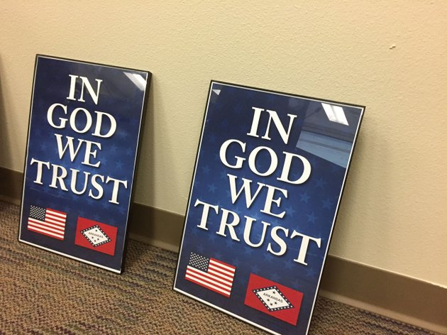 northwest-arkansas-democrat-gazettedave-perozek-two-of-the-framed-in-god-we-trust-posters-presented-to-bentonville-school-board-members-at-their-feb-19-meeting-are-seen-here-state-rep-jim-dotson-r-bentonville-and-ray-brust-a-representative-of-american-legion-post-77-presented-the-posters-to-the-board-they-said-nearly-900-more-are-being-donated-to-bentonville-schools-for-display-in-classrooms-and-libraries