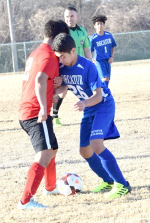 Westside Eagle Observer/MIKE ECKELS Jason Orellana (Decatur 26) and a Pirate player go head to head over a loose ball during the March 1 Decatur-Locust Grove boys' soccer match at Bulldog Stadium in Decatur. The varsity boys won their first match of the season with an 11-0 shutout of Locust Grove.