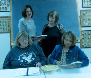 Westside Eagle Observer/SUSAN HOLLAND Jen Thurlo and Lavon Stark (standing), Nancy Amos and Charlene Newell, members of Northwest Arkansas Cattlewomen, browse through cookbooks looking for new pie recipes as their annual benefit pie auction draws near. The event is scheduled for 6:30 p.m. Tuesday, March 14, at the Maysville Community Building.