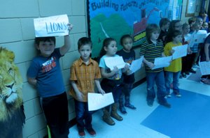 Westside Eagle Observer/SUSAN HOLLAND Students at Glenn Duffy Elementary School hold up signs they made to cheer on the Gravette Lady Lions when they visited the school Wednesday morning before their departure for the state basketball tournament. Students made the signs to show their support for the team at the sendoff organized by Taos Jones, assistant high school principal.