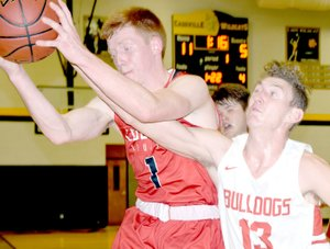 RICK PECK/SPECIAL TO MCDONALD COUNTY PRESS McDonald County's Blake Gravette takes a rebound away form Carl Junction's Will Bebee during the Mustangs' 58-41 loss on March 1 in the district semifinals at Cassville High School.