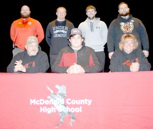 RICK PECK/SPECIAL TO MCDONALD COUNTY PRESS Trey Black (front row, center) recently signed a letter of intent to play football at Friends University in Wichita, Kan. Front row, left to right: Kelly Black (dad), Trey Black and Kristie Black (mom). Back row: MCHS football coaches Craig Collins, Sean McCullough, Kellen Hoover and Chris Kane.