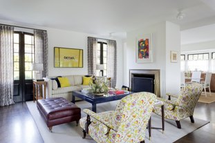 """This photo provided by Amy Sklar Design shows two chairs in a room with floral prints. """"As a designer, I love bold floral prints that feel modern but wink to the classics,"""" says designer Sklar. """"The profile of this particular chair is very traditional, so adding a poppy pattern here makes it feel much more current, timeless and fun."""" Mixing styles is a hot trend now in décor and design. (Amy Bartlam/Amy Sklar Design via AP)"""
