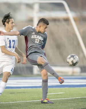 Ben Goff/NWA Democrat-Gazette Brayan Flores, left, of Rogers watches as Gerson Matias of Siloam Springs makes a play with the ball Tuesday at Whitey Smith Stadium in Rogers.