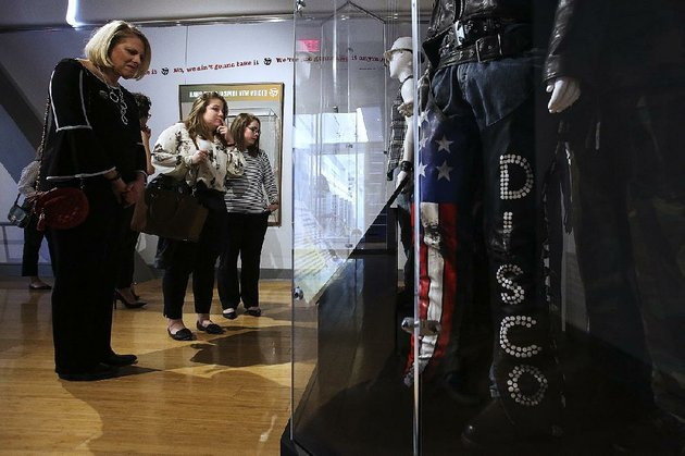 visitors-katy-nelson-left-of-fayetteville-catherine-campos-center-of-miami-and-mollie-may-henager-of-little-rock-check-out-the-disco-display-thats-part-of-the-louder-than-words-rock-power-and-politics-exhibit-before-former-president-bill-clintons-talk-at-the-clinton-presidential-center-on-sunday-in-little-rock