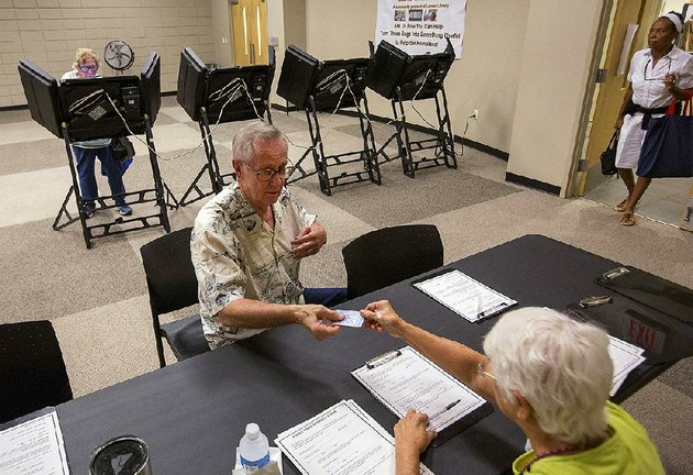 ken-bushe-hands-a-photo-id-to-a-poll-worker-at-laman-library-in-north-little-rock-during-voting-for-a-north-little-rock-sales-tax-increase-in-august-it-was-the-first-election-after-the-voter-id-law-went-into-effect