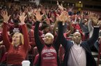 Arkansas Razorbacks head coach Mike Anderson (right) and his wife Marcheita Anderson (center) call the hogs during the NCAA selection show, Sunday, March 11, 2018 at Bud Walton Arena in Fayetteville. The Razorbacks will play Butler in Detroit on Friday