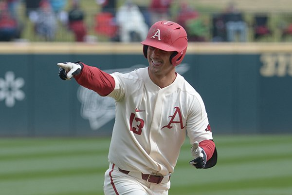 Arkansas' Jordan McFarland points toward the Razorbacks dugout following a home run on Sunday March 11, 2018 at Baum Stadium in Fayetteville. Arkansas beat Kent State 11-4.
