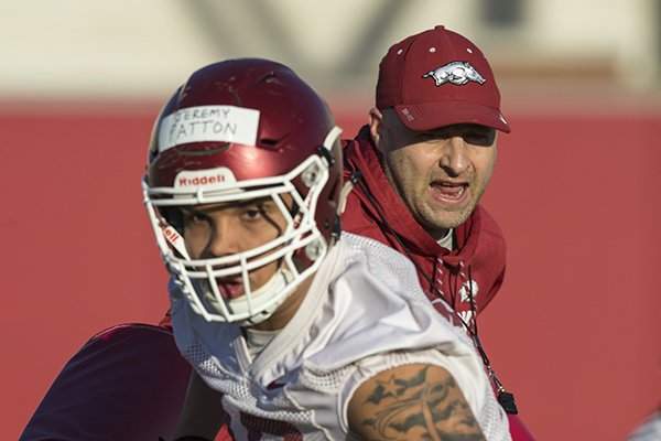 Barry Lunney, Jr., Arkansas tight ends coach, works with tigh end Jeremy Patton on a drill Thursday, March 1, 2018, during Arkansas spring football practice at the Fred W. Smith Football Center in Fayetteville.