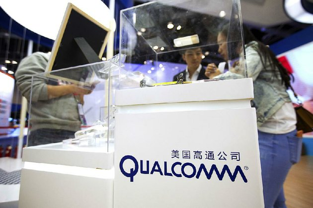 visitors-look-at-a-display-booth-for-qualcomm-at-the-global-mobile-internet-conference-in-beijing-last-spring-shares-of-qualcomm-slid-almost-5-percent-tuesday
