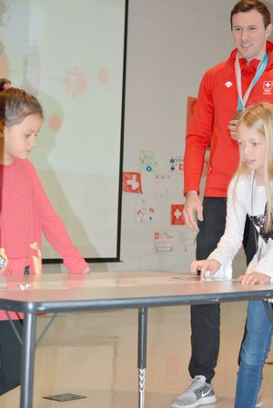 Graham Thomas/Herald-Leader Allen Elementary second-grader Ella Burnett takes a turn at tabletop curling as fellow second-grader Sophia Jones, left, and Switzerland's Dominik Maerki look on Tuesday at Allen Elementary.
