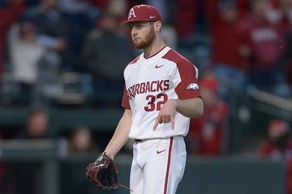 Arkansas pitcher Matt Cronin flashes the downward horns sign after recording the final out during a game against Texas on Wednesday, March 14, 2018, in Fayetteville.