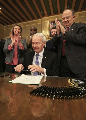 Gov. Asa Hutchinson, flanked by Rep. Michelle Gray, R-Melbourne, and Sen. Ron Caldwell, R-Wynne, signs the pharmacy benefit bill Thursday at the state Capitol.