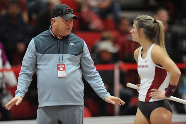 Arkansas assistant coach Bryan Compton speaks with Victoria Weeks as Weeks competes in the pole vault Friday, Jan. 15, 2016, during the Arkansas Invitational at the Randal Tyson Track Center.