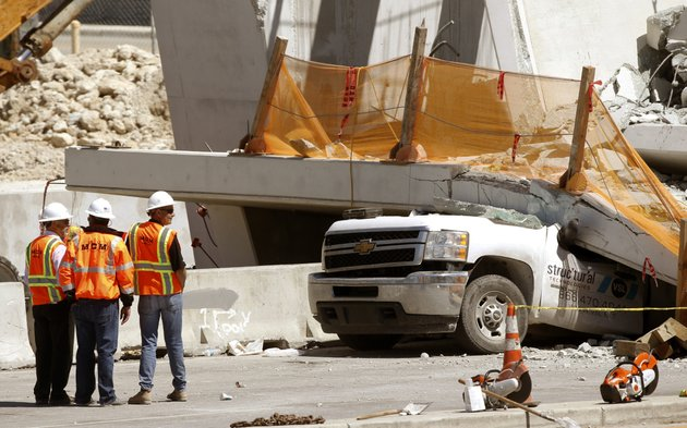 workers-stand-next-to-a-section-of-a-collapsed-pedestrian-bridge-friday-march-16-2018-near-florida-international-university-in-the-miami-area-the-new-pedestrian-bridge-that-was-under-construction-collapsed-onto-a-busy-miami-highway-thursday-afternoon-crushing-vehicles-beneath-massive-slabs-of-concrete-and-steel-killing-and-injuring-several-people-authorities-said-ap-photowilfredo-lee
