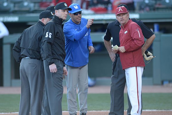 Arkansas coach Dave Van Horn and Kentucky coach Nick Mingione meet with umpires prior to a game Friday, March 16, 2018, in Fayetteville.