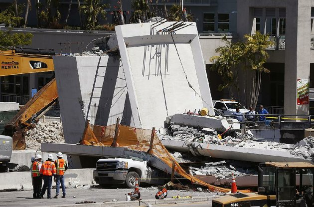 workers-in-miami-stand-next-to-a-section-of-a-collapsed-pedestrian-bridge-near-florida-international-university-on-friday-two-days-before-thursdays-collapse-an-engineer-had-left-a-voice-mail-at-the-state-transportation-agency-noting-cracks-in-the-concrete