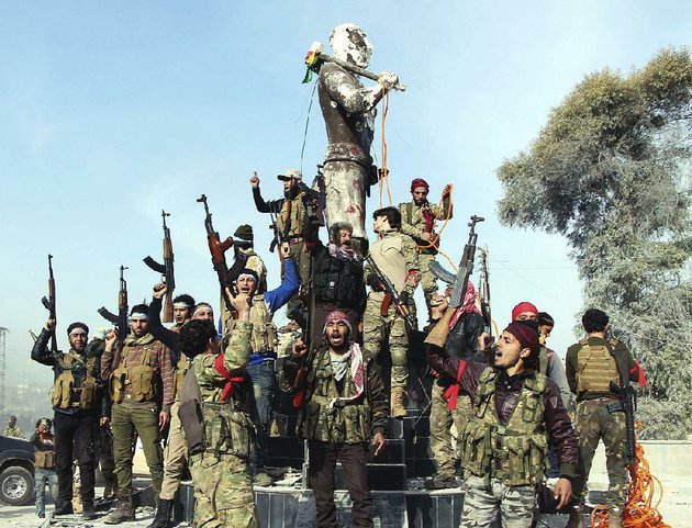 turkey-backed-free-syrian-army-soldiers-celebrate-around-a-statue-of-kawa-a-mythological-figure-in-kurdish-culture-after-capturing-the-enclave-of-afrin-syria-from-the-kurds-on-sunday-the-soldiers-planned-to-destroy-the-statue