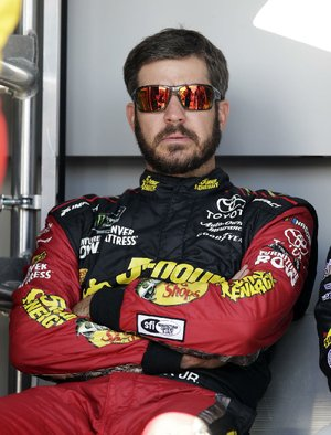 Martin Truex Jr. (78) sits in the shade before a NASCAR Cup Series auto race on Sunday, March 11, 2018, in Avondale, Ariz. (AP Photo/Rick Scuteri)