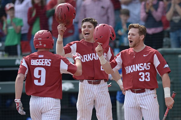 Arkansas shortstop Jax Biggers (9) is congratulated at the plate by second baseman Carson Shaddy (center) and Grant Koch (33) after hitting a 3-run home run against Kentucky Saturday, March 17, 2018, during the fifth inning at Baum Stadium in Fayetteville.