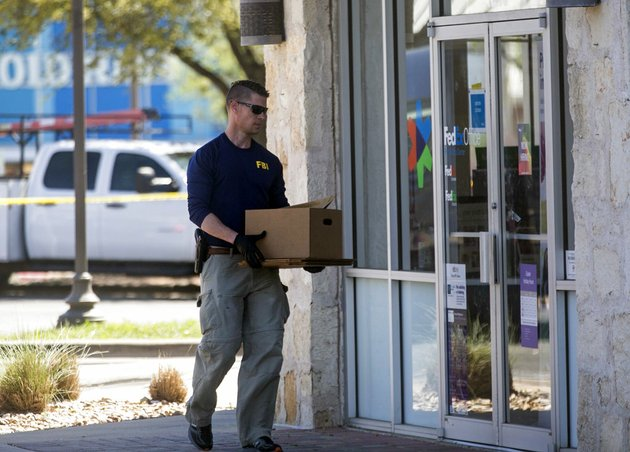 an-fbi-official-carries-items-into-a-fedex-office-store-tuesday-march-20-2018-in-the-southwest-austin-suburb-of-sunset-valley-texas-as-authorities-investigate-a-recent-string-of-package-bombs