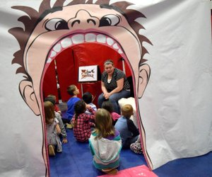 Westside Eagle Observer/MIKE ECKELS Inside a giant mouth, Allyson Carter, a teacher at Decatur Northside Elementary, shows students proper dental hygiene during the Farm and You program in the safe room at Northside March 8.