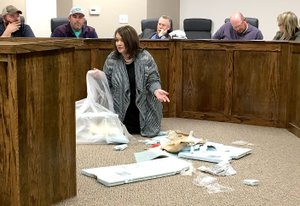 Westside Eagle Observer/RANDY MOLL Michelle Rieff, Highfill councilwoman and Highfill resident, questions the council about trash she picked up on her property from the home construction in Highfill by Rausch Coleman Homes and Schuber Mitchell Homes. She asked the city why nothing was being done to prevent the construction trash from blowing onto the property and into the pastures of neighbors to the construction, pointing out that some of the trash is hazardous if ingested by calves or livestock.