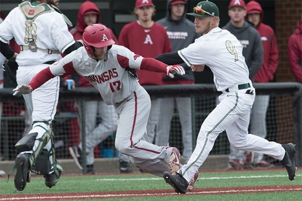 Arkansas designated hitter Luke Bonfield is tagged out by Charlotte infielder Tommy Bullock during a game Wednesday, March 21, 2018, at Hayes Stadium in Charlotte, N.C.