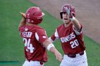 Arkansas second baseman Carson Shaddy (20) congratulates center fielder Dominic Fletcher (24) after Fletcher hit a home run during a game against Florida on Friday, March 23, 2018, in Gainesville, Fla.