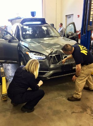 Investigators examine the self-driving Uber SUV that struck and killed a woman last week in Tempe, Ariz., in this photo provided by the National Transportation Safety Board.
