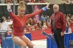Arkansas' Sarah Shaffer competes Friday, Jan. 12, 2018, in the bars portion of the Razorbacks' meet with Kentucky in Barnhill Arena in Fayetteville. Arkansas coach Mark Cook is shown watching in the background.