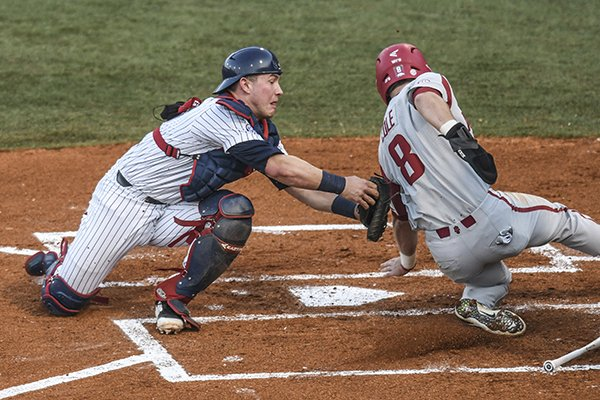 Mississippi catcher Cooper Johnson, left, tags out Arkansas' Eric Cole, right, in the first inning of an NCAA college baseball game in Oxford, Miss. on Friday, March 30, 2018. (Bruce Newman, Oxford Eagle via AP)