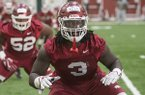 McTelvin Agim, Arkansas defensive lineman, warms up Thursday, March 1, 2018, during Arkansas spring football practice at the Fred W. Smith Football Center in Fayetteville.