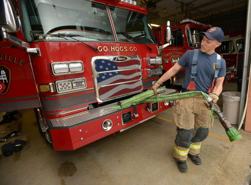 NWA Democrat-Gazette/ANDY SHUPE Martin Striefler, firefighter with the Fayetteville Fire Department, rewinds a hose Thursday in the department's central ...