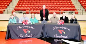 "Pam Jowers Special to the Enterprise-Leader Farmington seniors Zach Newman (left behind Cardinal helmet) with his parents, Willie and Stephanie Newman, accompanied by ; and Jacob Gray (right behind helmet) with his parents, Bill and Karen Gray; signed national letters of intent to continue their football careers in college on Feb. 7. Farmington head coach Mike Adams (standing) introduced the players. Newman signed as an offensive lineman with Arkansas Tech while Gray signed as an ""H-back"" with Henderson State."