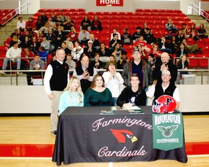 MARK HUMPHREY ENTERPRISE-LEADER Farmington senior Trey Waggle, seated with his parents, Josh and Kelley Waggle, and sister Paige Waggle, a Farmington freshman, signed a National letter of intent to play college football as a deep-snapper for Northeastern University of Tahlequah, Okla., on Wednesday, March 7, at Cardinal Arena. Witnessing the occasion were (standing from left): Farmington football coach Mike Adams, Farmington Mayor Ernie Penn, Trey's maternal grandparents Debra and Brad Rice, and long-time family friend Sam Sparkman.