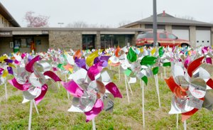 Keith Bryant/The Weekly Vista Bella Vista police officers and firefighters teamed up with volunteers Monday to place 380 pinwheels, each representing a confirmed case of child abuse in Benton County, in front of the Bella Vista Police Department. This is down from last year, which had 439 confirmed cases.