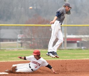 RICK PECK/SPECIAL TO MCDONALD COUNTY PRESS Shiloh Christian's shortstop Connor Clark leaps for a high throw while McDonald County's Caleb Curtis steals second base during the Mustangs' 4-3 win on March 26 at MCHS.
