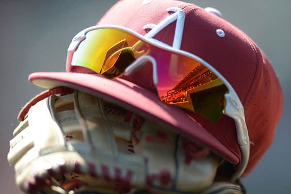an-arkansas-hat-and-glove-sit-in-the-dugout-prior-to-a-game-against-louisiana-monroe-on-wednesday-april-4-2018-in-fayetteville