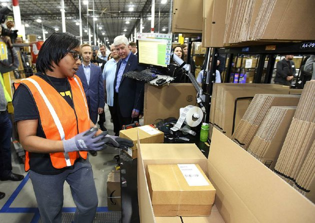 anjoli-wilson-packages-products-as-michigan-lt-gov-brian-calley-center-and-gov-rick-snyder-watch-during-the-grand-opening-of-amazons-new-fulfillment-center-in-livonia-in-march