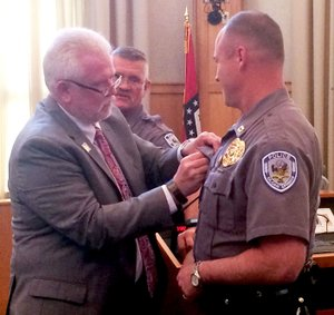 Janelle Jessen/Herald-Leader City administrator Phillip Patterson pinned an FBI Academy professional development ribbon on Captain Todd Brakeville's uniform during the city board meeting on Tuesday as Police Chief Jim Wilmeth looked on. Brakeville recently graduated from the FBI Academy program in Quantico, Va.
