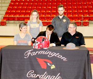 LYNN KUTTER ENTERPRISE-LEADER Farmington senior Caleb Williams signs a national letter of intent to play football and run track for Hendrix College of Conway. Caleb's family (from left): Melisa Williams (mother), Rebekah Williams (sister), Caleb, Josh Williams (brother), and Paul Williams (father) cheer him on.