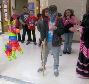 Westside Eagle Observer/SUSAN HOLLAND Students line up and wait their turn at striking the pinata at the GUE multicultural dinner Thursday, April 5, as one blindfolded young man prepares to take a whack at the colorful, candy-filled donkey.