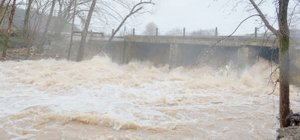 Keith Bryant/The Weekly Vista Floodwaters rush past the Lake Bella Vista Dam, just upstream from the streambank restoration project. The heavy rain that northwest Arkansas received late March, as well as other flood events, contribute to erosion of the creek bank.
