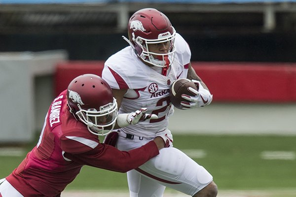 Arkansas running back Devwah Whaley tries to run through a tackle attempt of safety Santos Ramirez during the Razorbacks' spring game Saturday, April 7, 2018, in Little Rock.