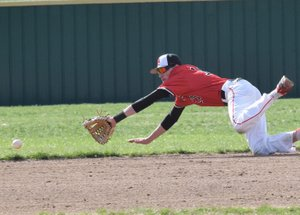 RICK PECK/SPECIAL TO MCDONALD COUNTY PRESS McDonald County shortstop Reece Cooper dives for a ground ball during the Mustangs' 2-1 loss to Webb City on April 4 at Webb City High School.