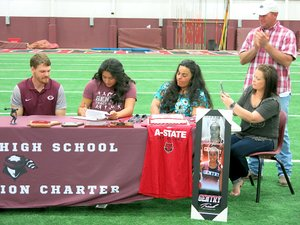 With assistant track coach Ethan Ramsey (left) looking on, Chastery Fuamatu, a Gentry senior and holder of state titles, signs her letter of intent to attend Arkansas State University, and throw the shot and discus there, during ceremonies at Gentry High School on Thursday, April 12, 2018. Her mother Alexandria Fuamatu and family sponsors Ashley and Holly Hays watch and applaud.