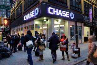 In this January 2015 file photo, people walk past a branch of Chase bank, in New York. JPMorgan Chase & Co. reports earnings Friday. (AP Photo/Mark Lennihan, File)