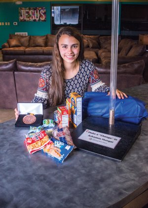 Jameson Archer, 14, has been recognized as a Distinguished Finalist in the Prudential Spirit of Community Awards program for her initiative to fight childhood hunger. She started a quarter drive to raise money for the Sheridan School District's food backpack program. Jameson's father, Joe Archer, built the collection boxes, which are 27 inches tall, using clear plastic piping attached to a base.