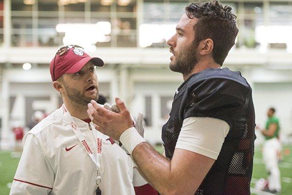 Arkansas offensive coordinator Joe Craddock, left, talks with quarterback Ty Storey during practice Saturday, March 3, 2018, in Fayetteville.